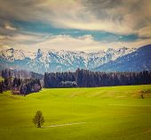 Vintage retro hipster style travel image of German idyllic pastoral countryside in spring with Alps