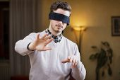 picture of blindfolded man  - Blindfolded young man at home in living room cannot see trying to find his way with his hands - JPG