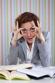 Businesswoman overloaded with work holding her eyes open