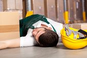 stock photo of overalls  - Dangerous accident at work in factory warehouse - JPG