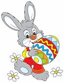 foto of cony  - Little rabbit carries a big colorfully painted Easter egg - JPG
