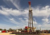 stock photo of derrick  - Land rig drilling under a beautiful cloudy sky in the New South Wales outback - JPG
