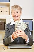 Elderly happy business woman with fan of dollar bills in the office