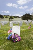 image of headstones  - Headstones floral arrangement and American Flags at National Military Cemetery - JPG