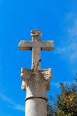 picture of inri  - Stone cross with INRI inscription on a marble column in Corinthian style on blue sky - JPG