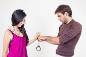 stock photo of kinky  - Handsome young man putting handcuffs on beautiful young girl isolated on white - JPG