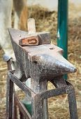 stock photo of anvil  - Old anvil with hammer on a metal stump - JPG