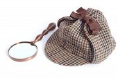 stock photo of sherlock  - Deerstalker Or Sherlock Holmes Cap And Vintage Magnifying Glass isolated on white background - JPG