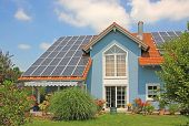 stock photo of cell  - modern new built house and garden rooftop with solar cells blue front with lattice window - JPG