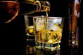 foto of reflection  - barman pouring whiskey in front of whiskey glass and bottles on black table with reflection - JPG