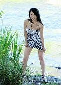 stock photo of skinny  - Skinny Asian American Woman Standing In Short Dress Outdoors - JPG