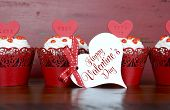 picture of red velvet cake  - Happy Valentine red velvet cupcakes with love messages on red vintage wood background with greeting card - JPG