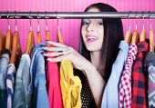 picture of wardrobe  - Time to refresh wardrobe young attractive surprised woman searching for clothing in a closet  - JPG