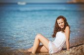 stock photo of nightie  - Young brunette woman with long wavy hair, wearing a white nightie lying in shallow water in the blue sea on a small round pebbles beach in the summer, wet shirt clung to her body.