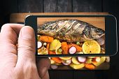 stock photo of bass fish  - Prepared Bass fish with vegetables and fruit from above on wooden background photographed by phone - JPG