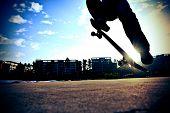 picture of skateboarding  - young skateboarder legs skateboarding jumping outdoor under blue sky - JPG