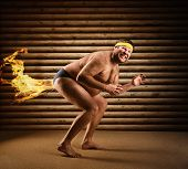 stock photo of fart  - Very strange naked man farts by fire - JPG