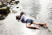 foto of accident victim  - View of a young woman washed up on rocks at the edge of a river - JPG
