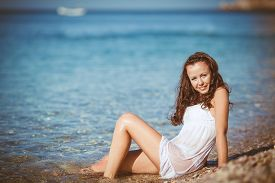 stock photo of nighties  - Young brunette woman with long wavy hair, wearing a white nightie lying in shallow water in the blue sea on a small round pebbles beach in the summer, wet shirt clung to her body.