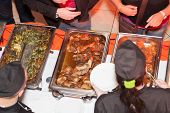 picture of catering  - Hands of cook serving food at a catered event - JPG