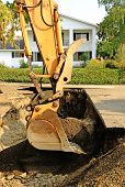 stock photo of track-hoe  - a large track hoe exchavator at the repair work following a broken water main leak from a fire hydrant base - JPG