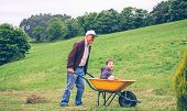 picture of wheelbarrow  - Portrait of happy senior man giving cute boy ride on a wheelbarrow - JPG