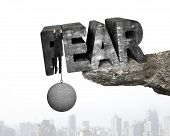 picture of stress-ball  - Man shackled by heavy concrete ball hanging on big 3D fear mottled word at the edge of cliff with urban scene background - JPG