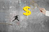 picture of rod  - Man jumping for 3D golden dollar sign bait on fishing rod hand holding with business concept doodles concrete wall background - JPG