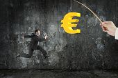 stock photo of rod  - Man running after 3D golden euro symbol bait on fishing rod hand holding with dark mottled concrete wall background - JPG