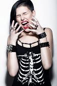 stock photo of gothic  - Screaming Girl with shaved head and blue hair in art gothic style with gothic accessories - JPG