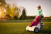 stock photo of golf bag  - Smiling woman golf player standing at fairway at sunset with her golf bag - JPG