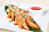 stock photo of shrimp  - grilled shrimp on skewers with sauce - JPG