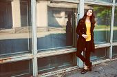 picture of blouse  - Young woman portrait with long brown hair dressed in black trenchcoat and yellow blouse - JPG