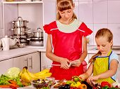 stock photo of pinafore  - Children little girl cooking vegetables on their own at kitchen - JPG
