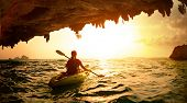 image of cave woman  - Young lady paddling the kayak in a sea near the cave exit - JPG