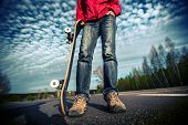 pic of skate board  - Rider standing on the asphalt road and holding skate board over the blue sky background - JPG