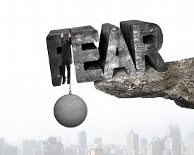 image of shackles  - Man shackled by heavy concrete ball hanging on big 3D fear mottled word at the edge of cliff with urban scene background - JPG