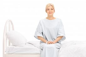 stock photo of hospital gown  - Blond female patient sitting on a hospital bed and looking at the camera isolated on white background - JPG