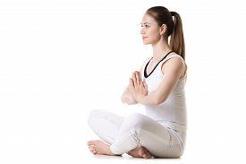 image of crossed legs  - Portrait of young beautiful girl in white sportswear doing yoga practice sitting cross - JPG