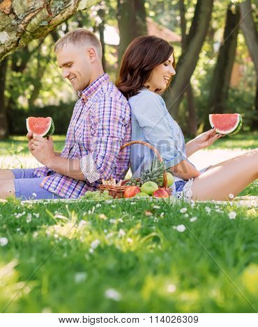 Beautiful couple leaning on each other backs and having a picnic in the garden.