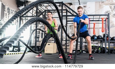 poster of Men with battle rope in functional training fitness gym