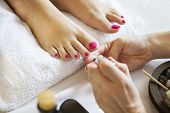 Woman In Nail Salon Receiving Pedicure By Beautician poster