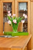 stock photo of vase flowers  - Bouquet of pink tulips flowers in glass vase on wooden table - JPG