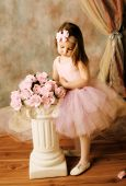 pic of cute little girl  - Adorable little girl dressed as a ballerina in a tutu standing next to pink roses - JPG