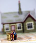 picture of eviction  - A couple who have just been evicted from there house carrying suitcases and walking past a pile of gold coins representing the outstanding debt they still have.