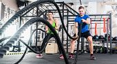 Men with battle rope in functional training fitness gym poster