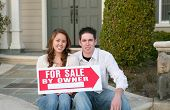 stock photo of real-estate agent  - a young couple selling their home holding a sale sign - JPG