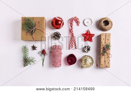 poster of Christmas decoration composition gift box pine cones ball spruce branches candle ribbon candy cane on white festive table isolated. New year winter holiday xmas. Top view flat lay copy space
