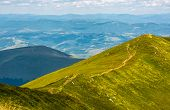 Footpath Through Mountain Ridge With Grassy Slopes poster