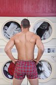 stock photo of indecent  - Muscular man in boxer shorts waits in front of washing machines - JPG